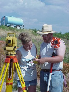 Teaching a young volunteer to use the total station surveying instrument.